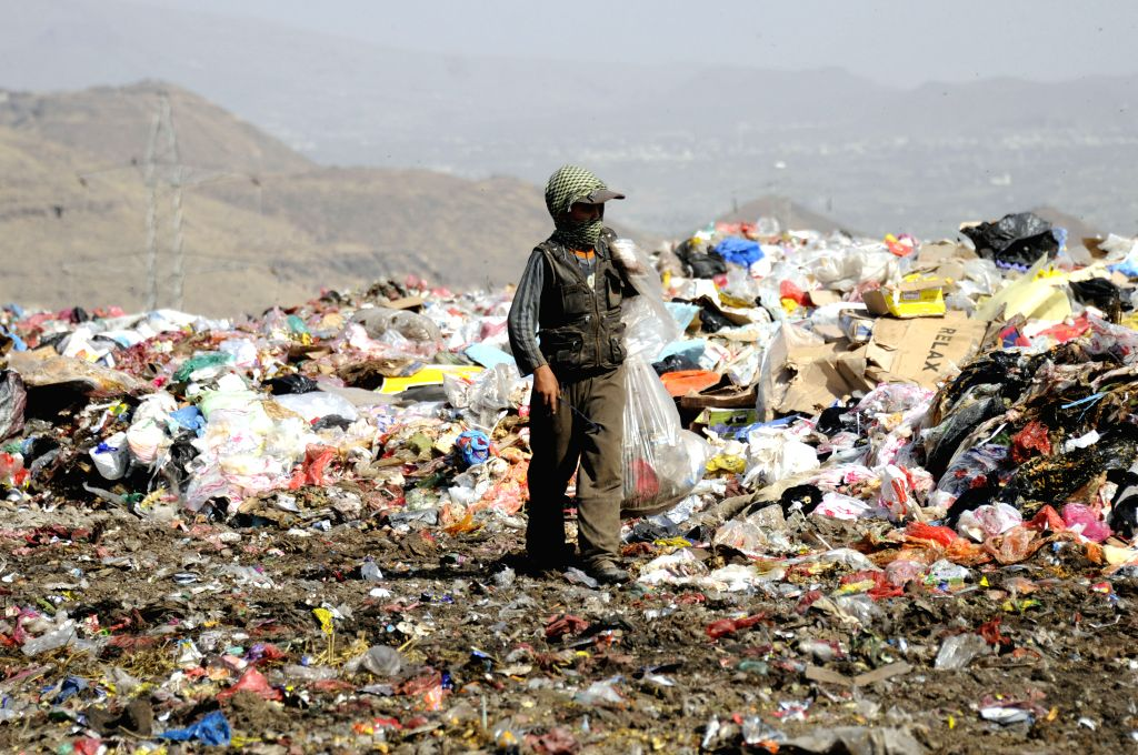 SANAA, March 12, 2017 - A boy walks at a garbage dump as he is searching for recyclable items to be sold to support his family in Sanaa, Yemen, on March 11, 2017.
