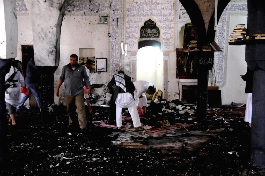 People clear a mosque after a suicide bomb attack in Sanaa, Yemen, March 20, 2015. A total of 88 people were killed and at least 100 others wounded on Friday in four ...