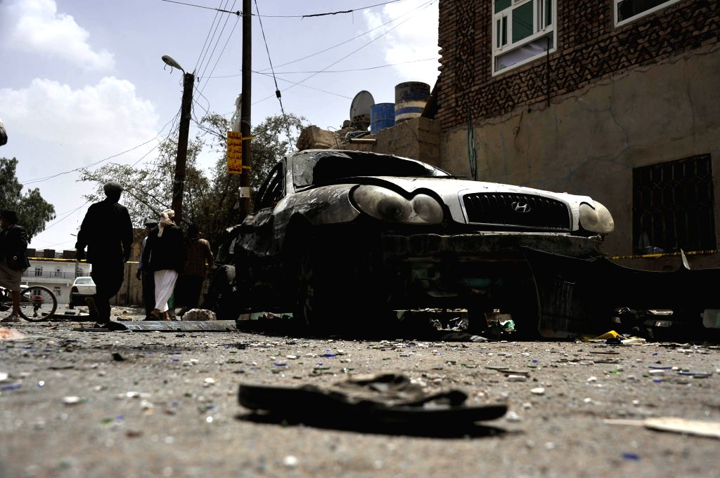 A damaged car and a shoe of a victim left on the ground are seen in Sanaa, Yemen, on March 21, 2015. The Islamic State (IS) carried out a series of suicide bombing ...