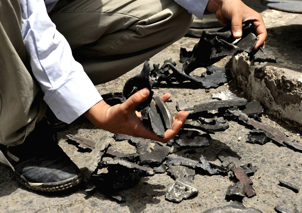 An official of the Sanaa international airport shows shrapnel of missiles on the runway of the airport that has been repaired, in Sanaa, Yemen, March 28, 2015. ...