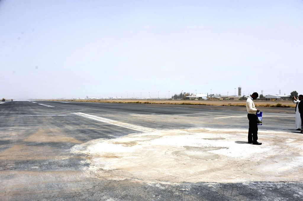 People stand on the runway that has been repaired, at Sanaa international airport in Sanaa, Yemen, March 28, 2015. Earlier on Thursday, a Saudi-led Arab coalition ...