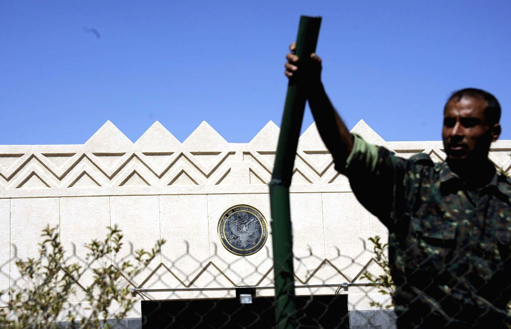 A Yemeni soldier stands in front of the U.S. embassy as the Yemeni authorities ordered to remove barriers, which were set up in front of the embassy after it was ...