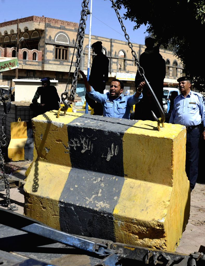 Yemeni security members remove barriers, which were set up in front of the U.S. embassy after it was closed in early February, in Sanaa, capital of Yemen, on March 4, ...