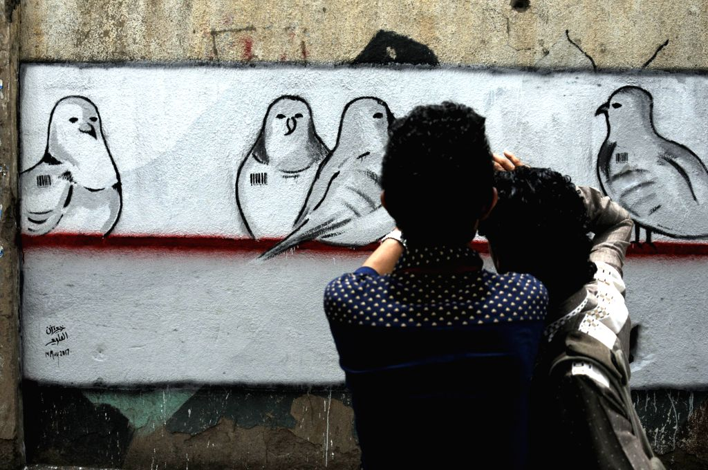 SANAA, May 14, 2017 - Two men look at the graffiti of peace doves on the wall in a street in Sanaa, capital of Yemen, on May 14, 2017. Yemeni activists drew graffiti in Sanaa's street to call for ...