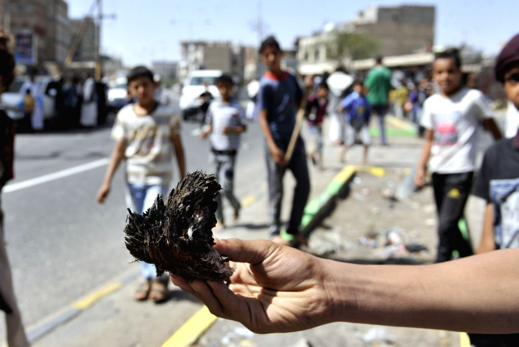 A man shows the wreckage of the bomb after a blast in Sanaa, Yemen, on May 9, 2014. A bomb blast targeted a military vehicle carrying Yemeni soldiers to checkpoints ...