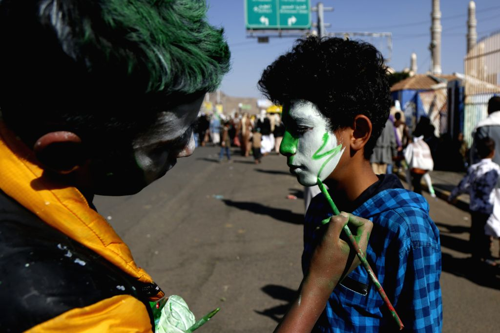 SANAA, Nov. 9, 2019 - A man paints a boy's face who takes part in a rally to celebrate the Islamic Prophet Muhammad's birthday in Sanaa, Yemen, on Nov. 9, 2019. Thousands of people packed al-Sabeen ...