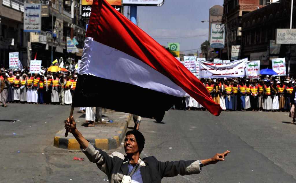 A Yemeni protestor holds up the Yemeni national flag during a demonstration in Sanaa, Yemen, on Sept. 1, 2014. Thousands of supporters of the Shiite Houthi group ...
