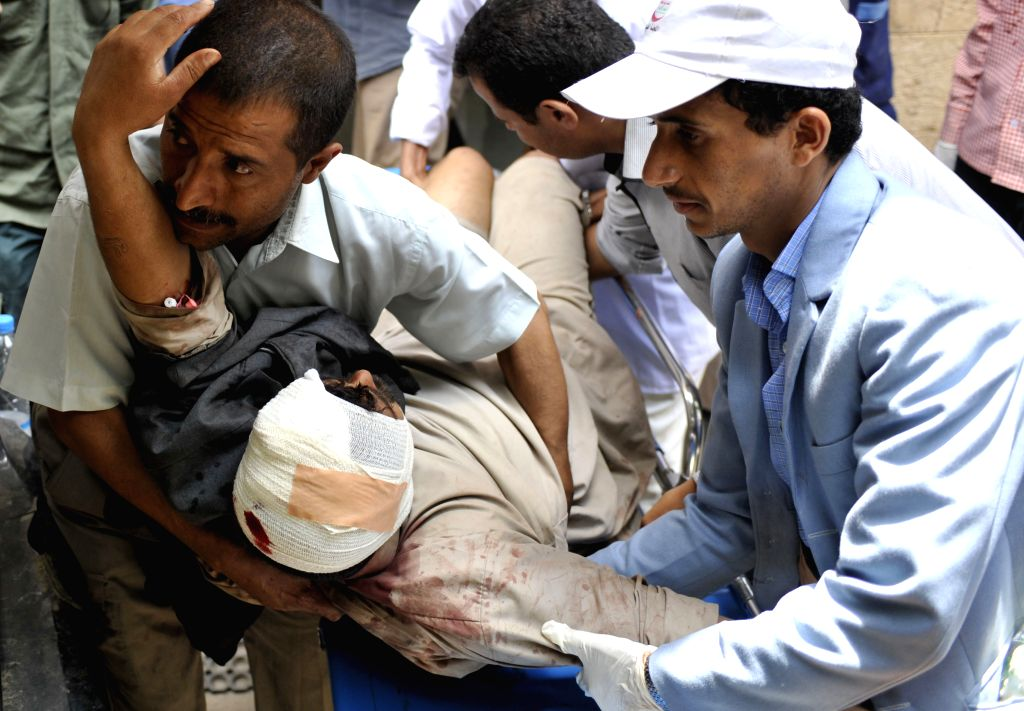 People carry a protester who was injured in clashes with riot police to a hospital in Sanaa, Yemen, on Sept. 9, 2014. At least one protester was killed and several ...