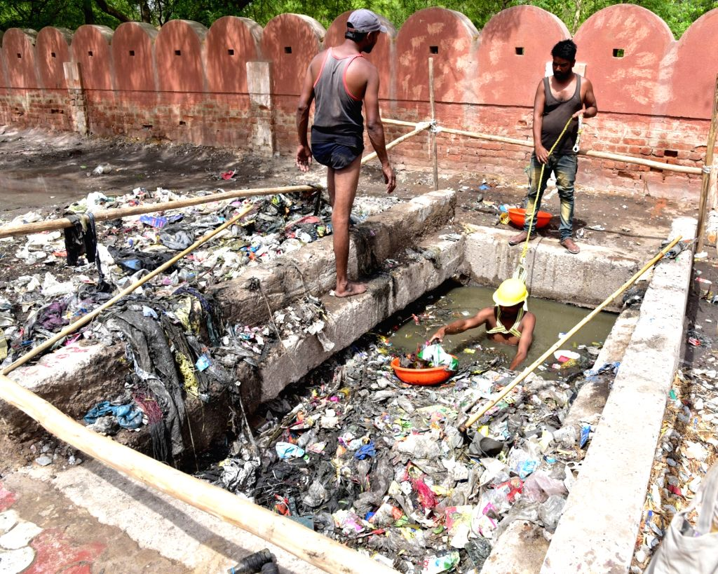 Sanitation workers busy cleaning a drain in Bikaner on May 12, 2019.
