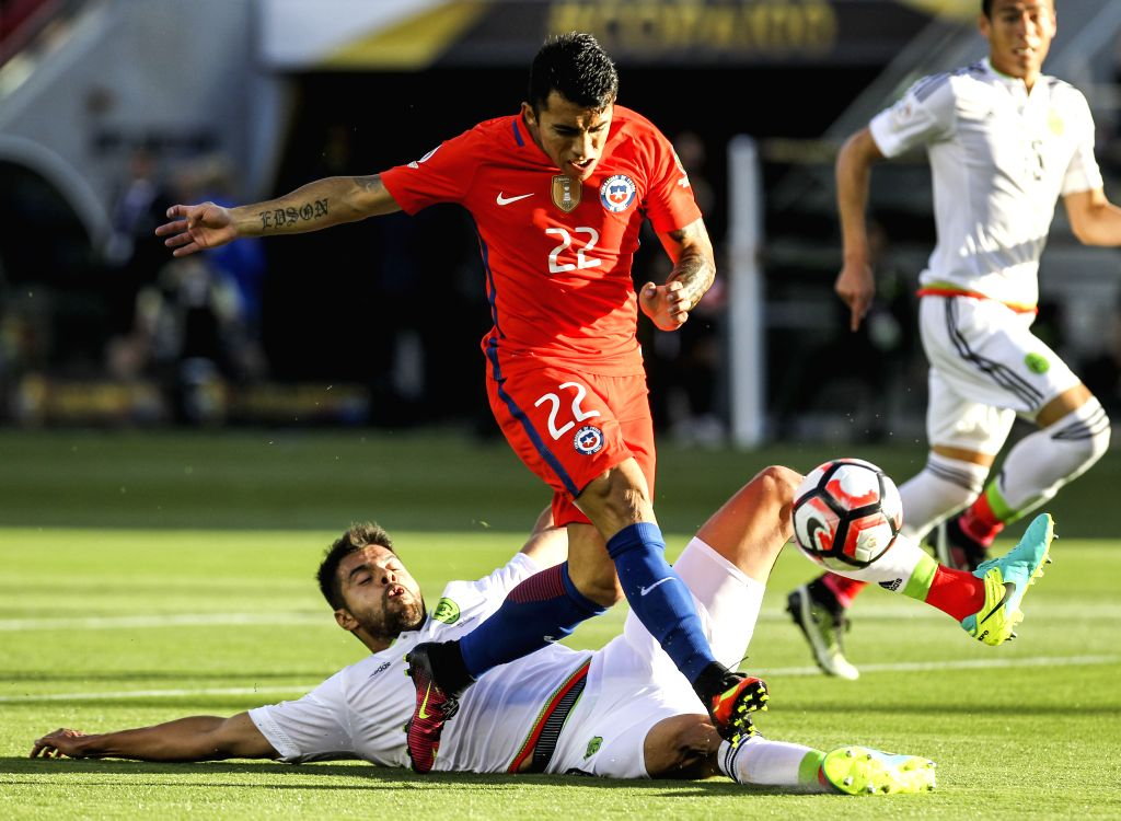 SANTA CLARA, June 19, 2016 - Edson Puch of Chile is tackled by Nestor Araujo of Mexico during their quarterfinal match of 2016 Copa America soccer tournament at the Levi's Stadium in Santa Clara, ...