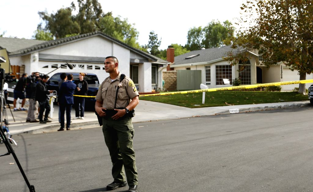 SANTA CLARITA (U.S.), Nov. 14, 2019 A sheriff stands guard near the suspect's home in Santa Clarita, Southern California, the United States, on Nov. 14, 2019. At least two students were ...