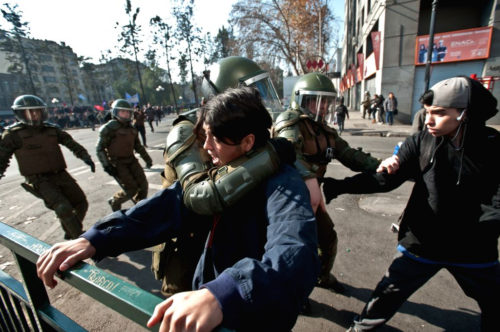 Members of the Riot Police arrest youngsters during a protest, in Santiago, Chile, on July 3, 2014. The Coordinator of Workers of the Transantiago called for a ...
