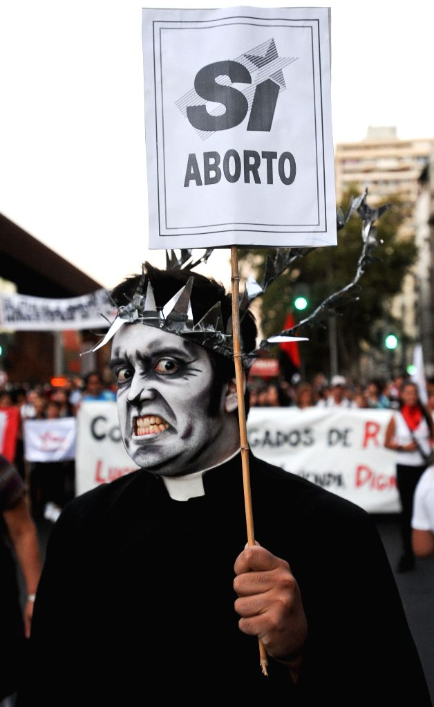 """A man holds a banner during a march called """"For a March 8 without clandestine abortions"""" to commemorate the International Women's Day, in Santiago, ..."""