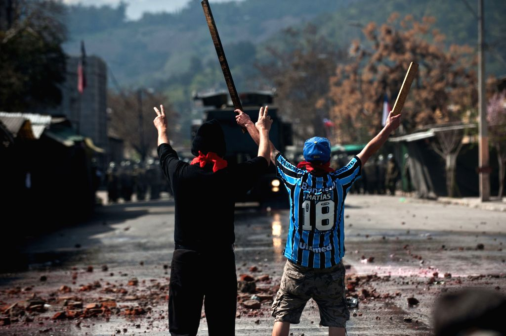 People take part in a clashes on the 41st anniversary of the military coup that brought Augusto Pinochet to power, in Santiago, capital of Chile, on Sept. 7, 2014.