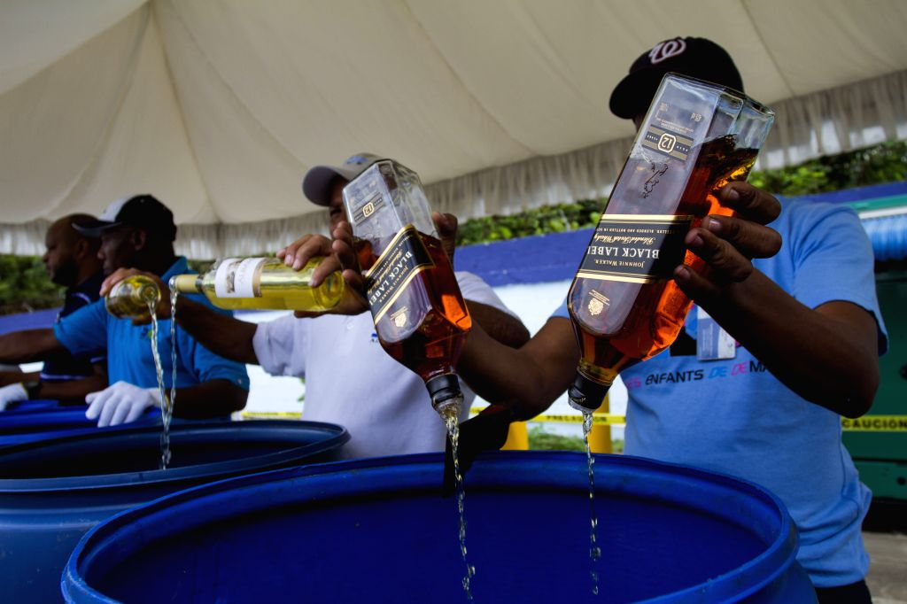 Employees of the Customs General Direction (DGA, for its acronym in Spanish), pour alcoholic beverages after being seized, in Santo Domingo, Dominican ...