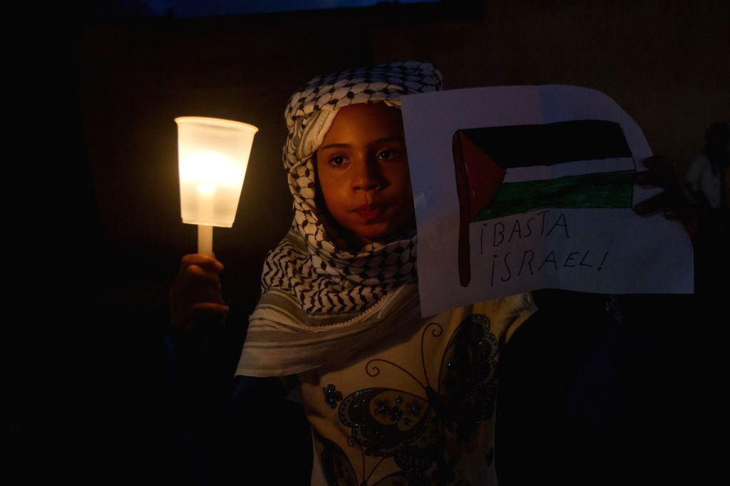 A girl holds a banner during a protest against the Israeli military operations in the Gaza Strip, in Santo Domingo, Dominican Republic, on Aug. 4, 2014. ...