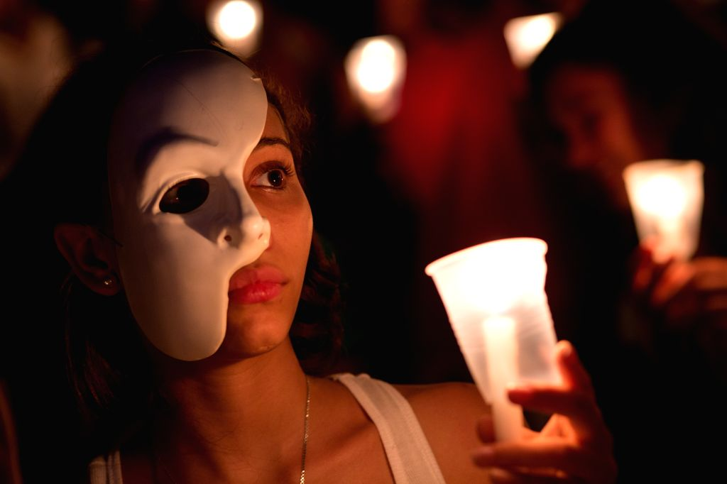 "A woman holds a candle in the event called ""Vigil for the Dignity of the Art"" in front of the Fine Arts Palace, in Santo Domingo, the Dominican ..."