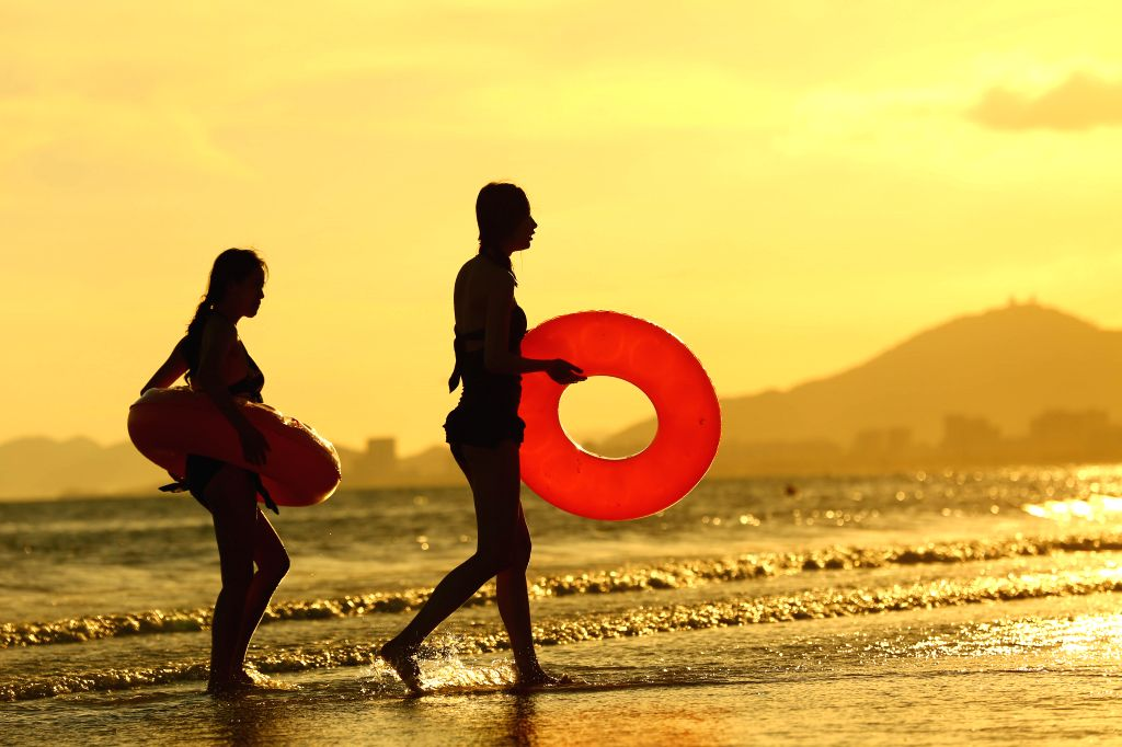 SANYA, June 25, 2016 - People enjoy leisure time amid sunset glow by the sea in Sanya, south China's Hainan Province, June 23, 2016.