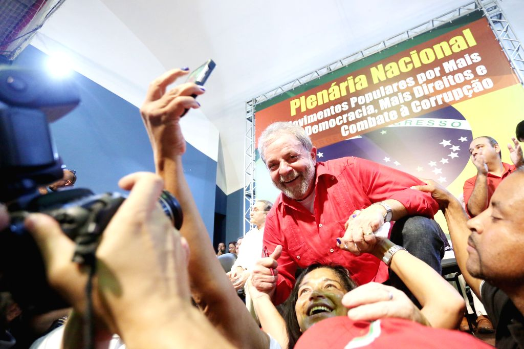 Brazil's former President Luiz Inacio Lula da Silva (C) interacts with the attendees during a meeting with Brazilian unions and social movements pro-government, ...