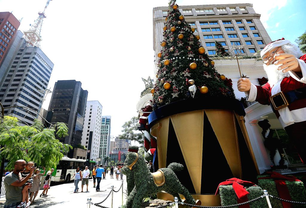Sao Paulo (Brazil): A man takes pictures of a Santa Claus statue on the Paulista Avenue, in Sao Paulo, Brazil, on Dec. 7, 2014.