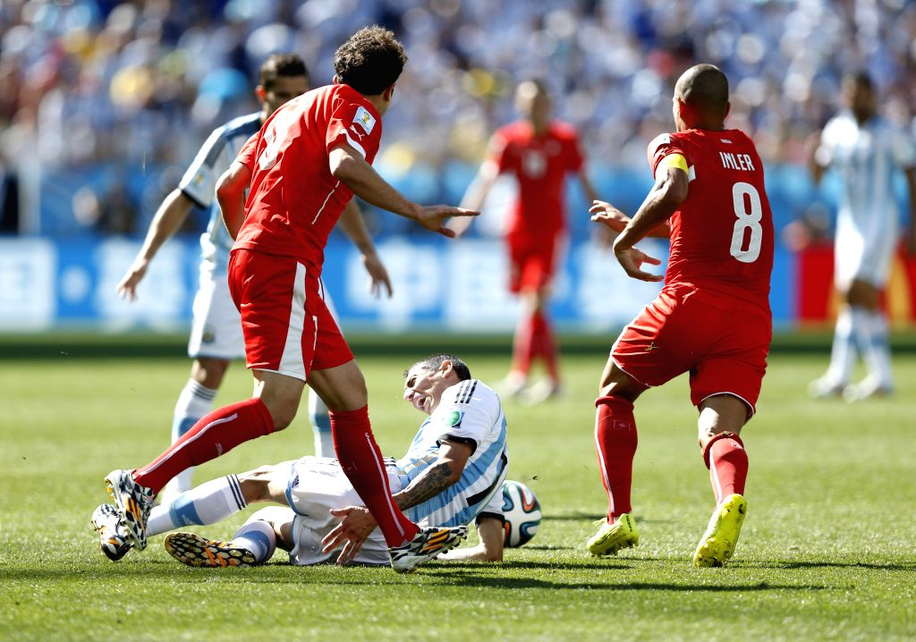 Argentina's Angel Di Maria (bottom) falls down during a Round of 16 match between Argentina and Switzerland of 2014 FIFA World Cup at the Arena de Sao Paulo ...