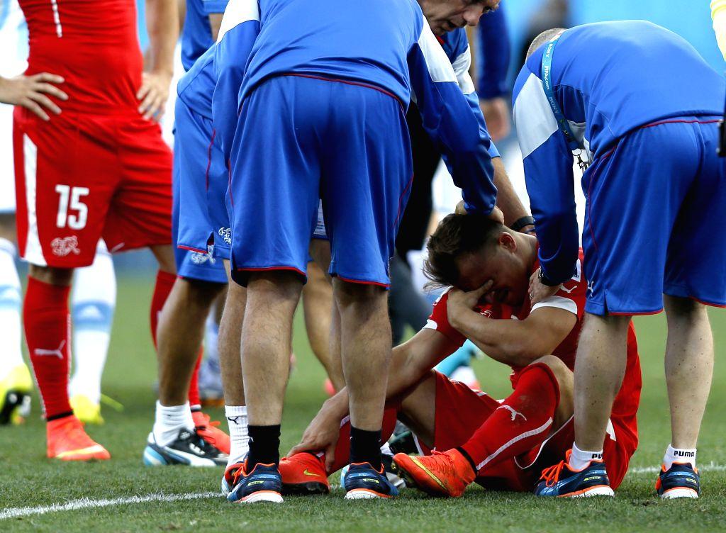Switzerland's Xherdan Shaqiri (bottom) reacts after a Round of 16 match between Argentina and Switzerland of 2014 FIFA World Cup at the Arena de Sao Paulo Stadium .