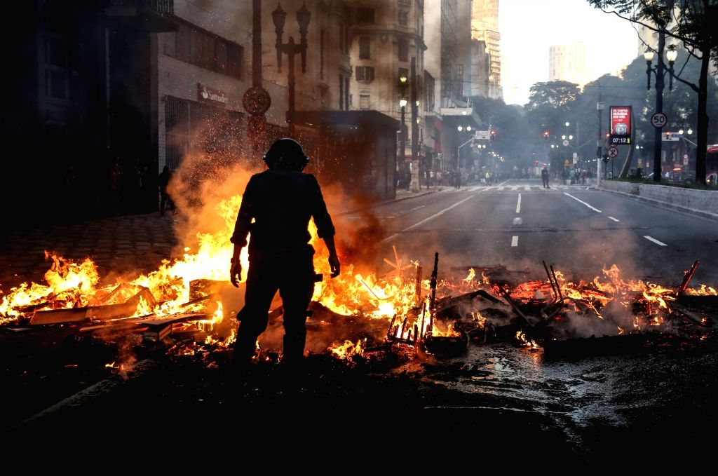 SAO PAULO, July 1, 2017 - A police officer stands next to a burning barricade set up by demonstrators in Sao Paulo, Brazil, on June 30, 2017. Nationwide protests on Friday rejected unpopular labor ...
