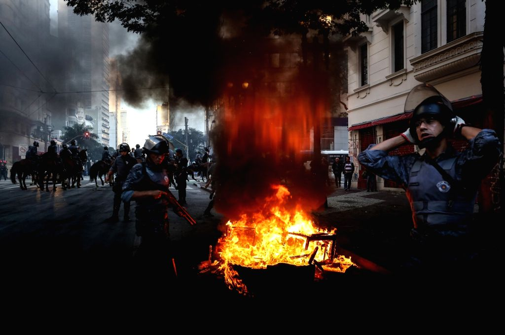 SAO PAULO, July 1, 2017 - Police officers stand next to a burning barricade set up by demonstrators in Sao Paulo, Brazil, on June 30, 2017. Nationwide protests on Friday rejected unpopular labor and ...
