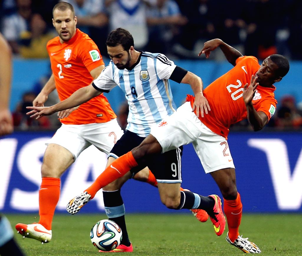 Argentina's Gonzalo Higuain (C) vies with Netherlands' Georginio Wijnaldum (R) during a semifinal match between Netherlands and Argentina of 2014 FIFA World Cup at