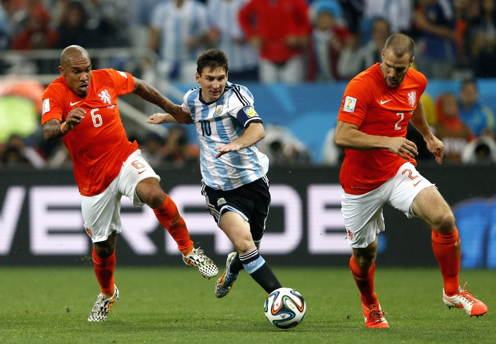 Argentina's Lionel Messi (C) vies with Netherlands' Nigel de Jong (L) and Ron Vlaar (R) during a semifinal match between Netherlands and Argentina of 2014 FIFA ...