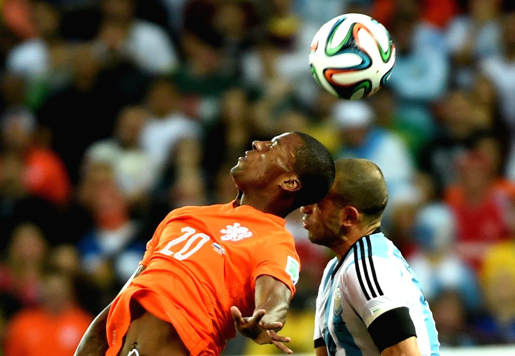 Netherlands' Georginio Wijnaldum competes for a header with Argentina's Javier Mascherano during a semifinal match between Netherlands and Argentina of 2014 FIFA ..