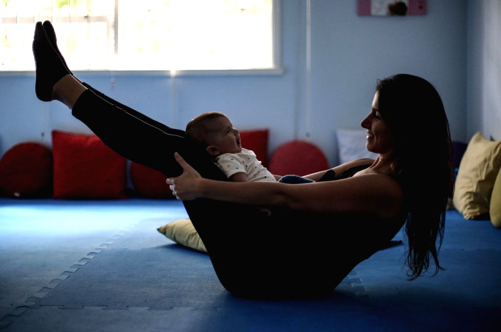 """SAO PAULO, June 21, 2017 - Image taken on June 8, 2017 shows a woman practicing yoga with her baby at """"Born Happy Space"""" in Sao Paulo, Brazil. According to instructors of yoga for babies, ..."""