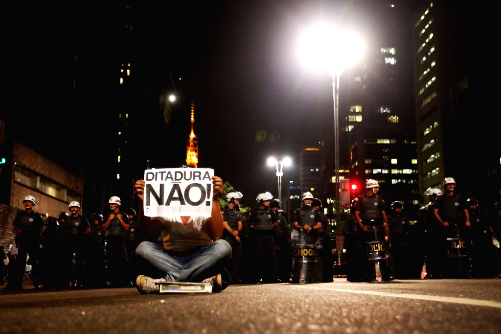 """A man holds a card board written with """"No Dictatorship"""" during a protest in object to the arrest of two demonstrators in Sao Paulo, Brazil, June 26, ..."""