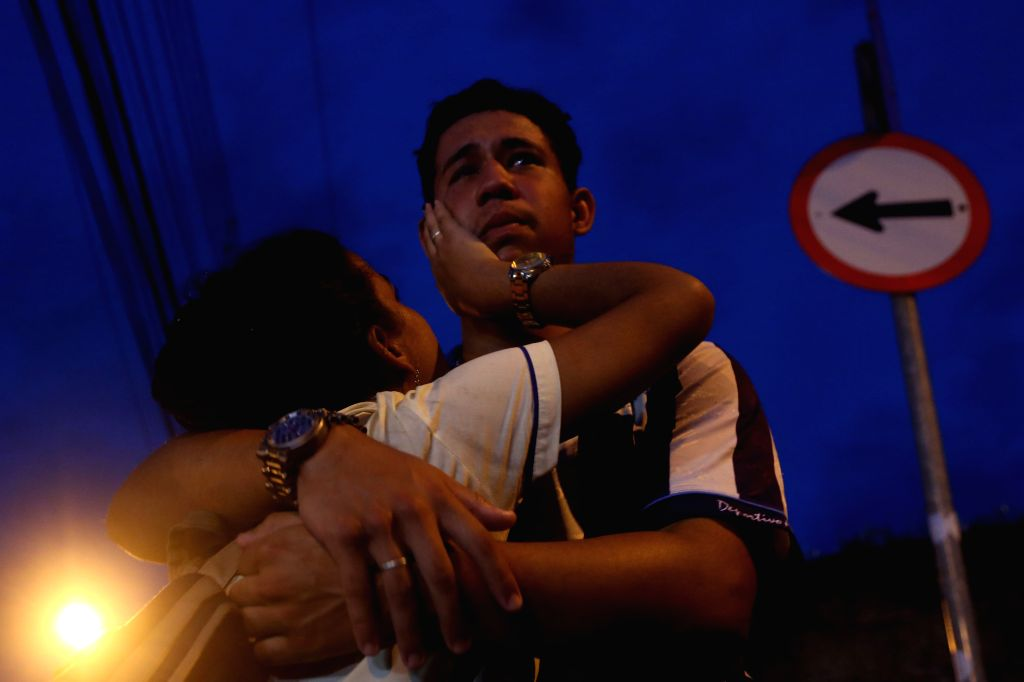 SAO PAULO, March 14, 2019 - A young man mourns for the dead outside the Raul Brasil Public School in Suzano, Sao Paulo, Brazil, on March 13, 2019. At least 10 people were killed and many more injured ...