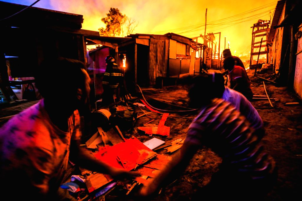 SAO PAULO, Sept. 14, 2016 - Firefighters and residents try to extinguish the fire at the community of Osasco on the outskirts of Sao Paulo, Brazil, on Sept. 13, 2016. According to Sao Paulo's fire ...