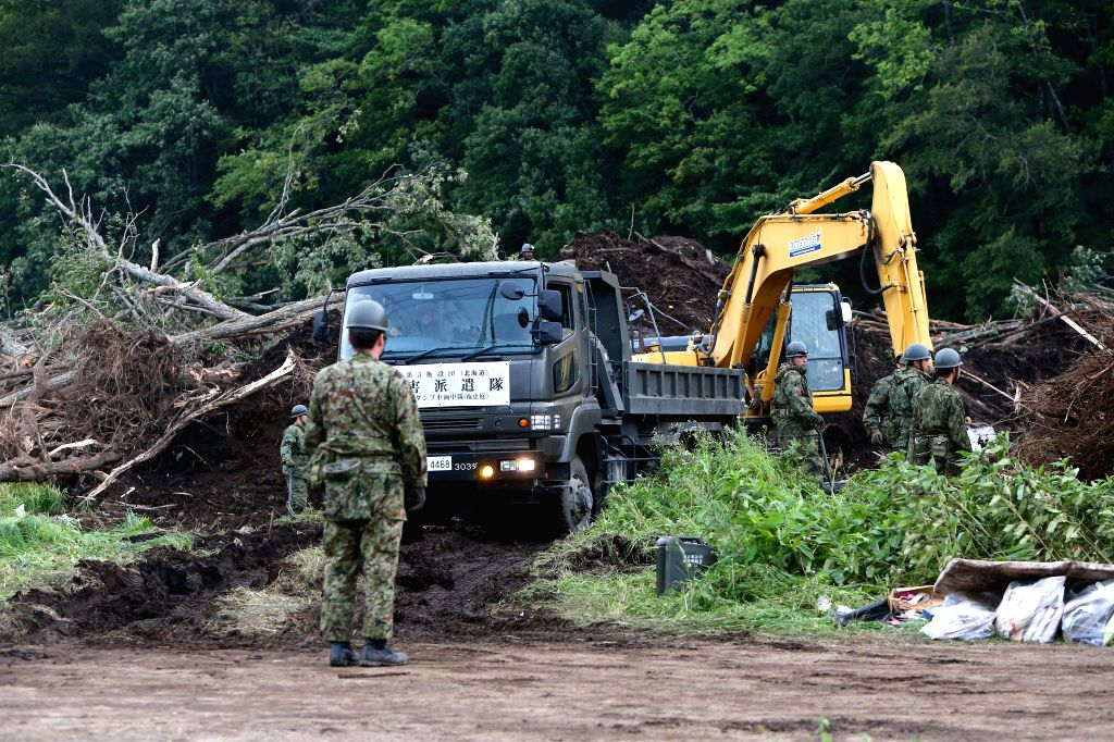 SAPPORO, Sept. 8, 2018 - Rescue members operate excavator and camion at a site of landslide due to earthquake in the town of Atsuma, Hokkaido prefecture, Japan, on Sept. 7, 2018. A total of 21 people ...