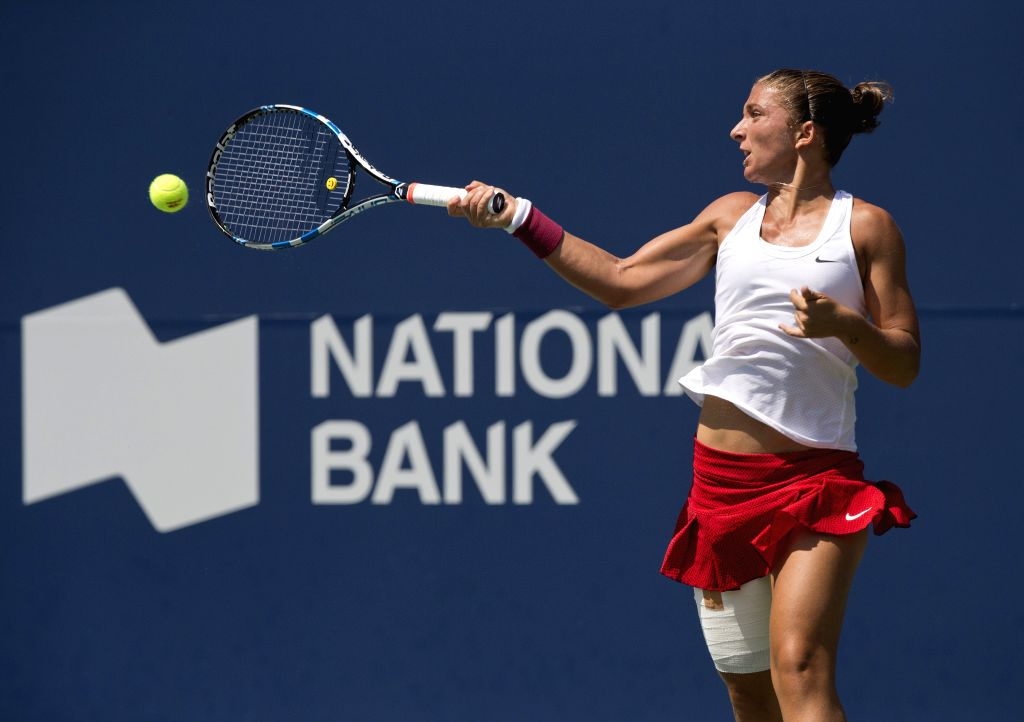 Sara Errani of Italy returns the ball against Simona Halep of Romania during their semifinal match of women's singles at the 2015 Rogers Cup in Toronto, Canada, ...