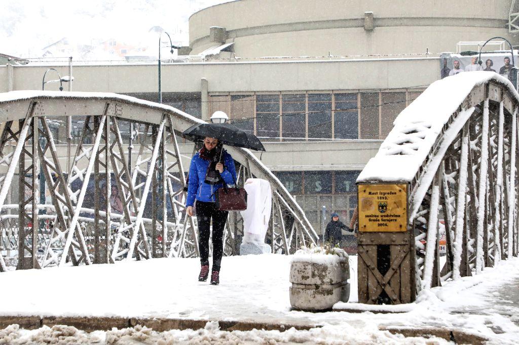 SARAJEVO, Feb. 13, 2018 - A woman walks over snow-covered bridge in Sarajevo, Bosnia and Herzegovina, on Feb. 13, 2018. Snowfall hit Sarajevo here on Tuesday.