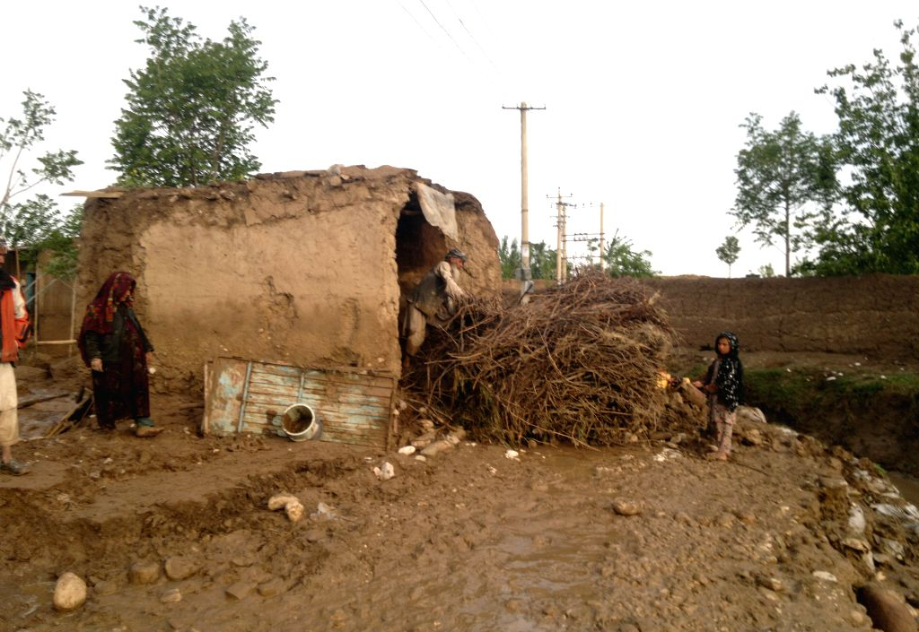 Afghans gather around their destroyed houses in Sarpul province, northern of Afghanistan, April 25, 2014. Heavy rains and flooding have claimed the lives of nearly .