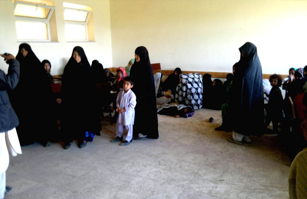 Afghans gather at a school in Sarpul province, northern of Afghanistan, April 25, 2014. Heavy rains and flooding have claimed the lives of nearly 40 people in ...