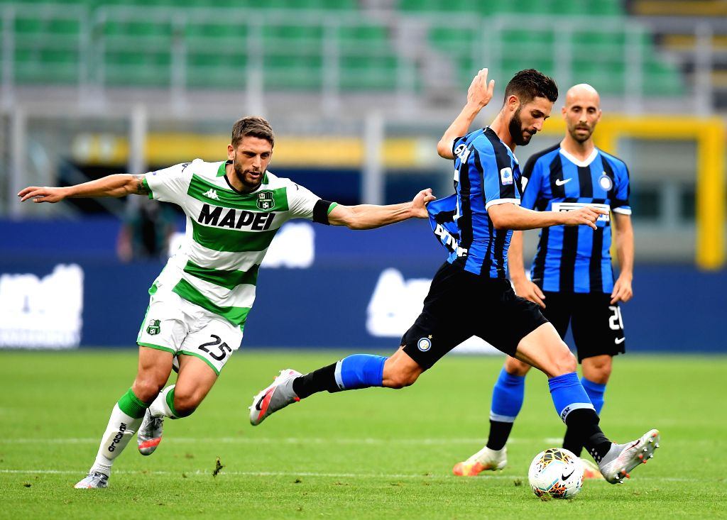 Sassuolo's Domenico Berardi (L) vies with FC Inter's Roberto Gagliardini (C) during a Serie A football match between FC Inter and Sassuolo in Milan, Italy, June 24, ...