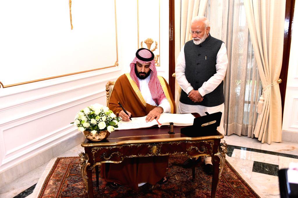 Saudi Crown Prince Mohammed bin Salman signs the Visitor's Book as Prime Minister Narendra Modi looks on, at Hyderabad House, in New Delhi, on Feb 20, 2019. - Narendra Modi