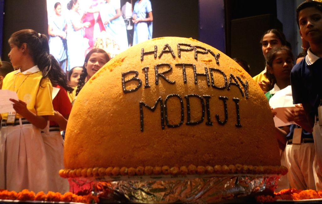 School children celebrate Prime Minister Narendra Modi's 68th birthday as Sulabh International founder Bindeshwar Pathak unveiled a 568 Kg laddu as part of the birthday celebration in New ... - Narendra Modi and Bindeshwar Pathak
