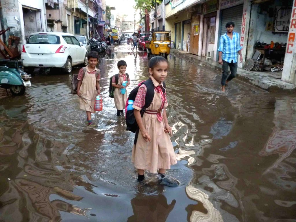 School children struggle through the flooded streets after heavy rain in Hyderabad on Oct 12, 2017.
