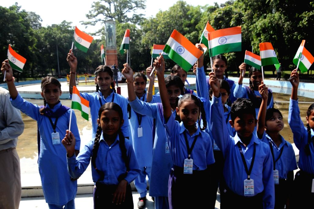 School children wave Indian national flags in front of a statue of Mahatma Gandhi on the occasion of the 152nd birth anniversary of the 'Father of the Nation' Mahatma Gandhi, in Amritsar on ...