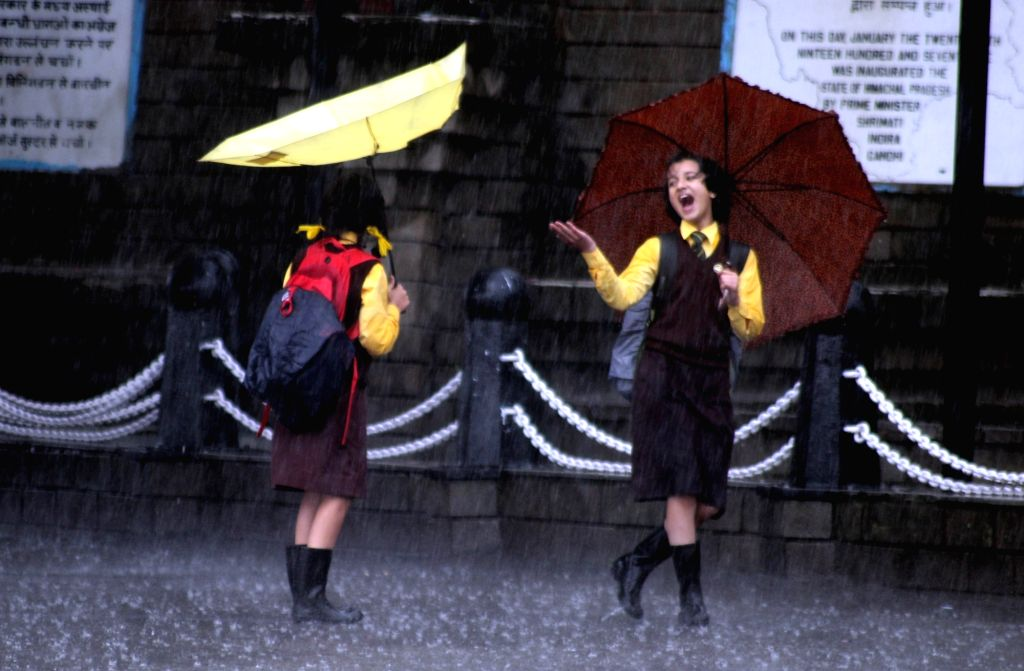 School girls enjoy themselves during rains, in Shimla on July 26, 2019.