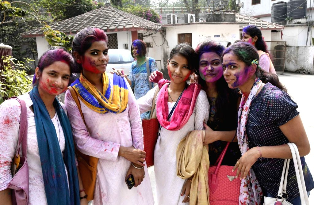School students apply colors on their face ahead of Holi in Patna on March 9, 2017.