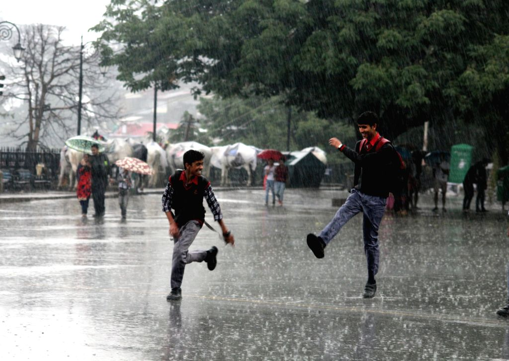School students enjoy themselves during rains in Shimla, on June 8, 2017.