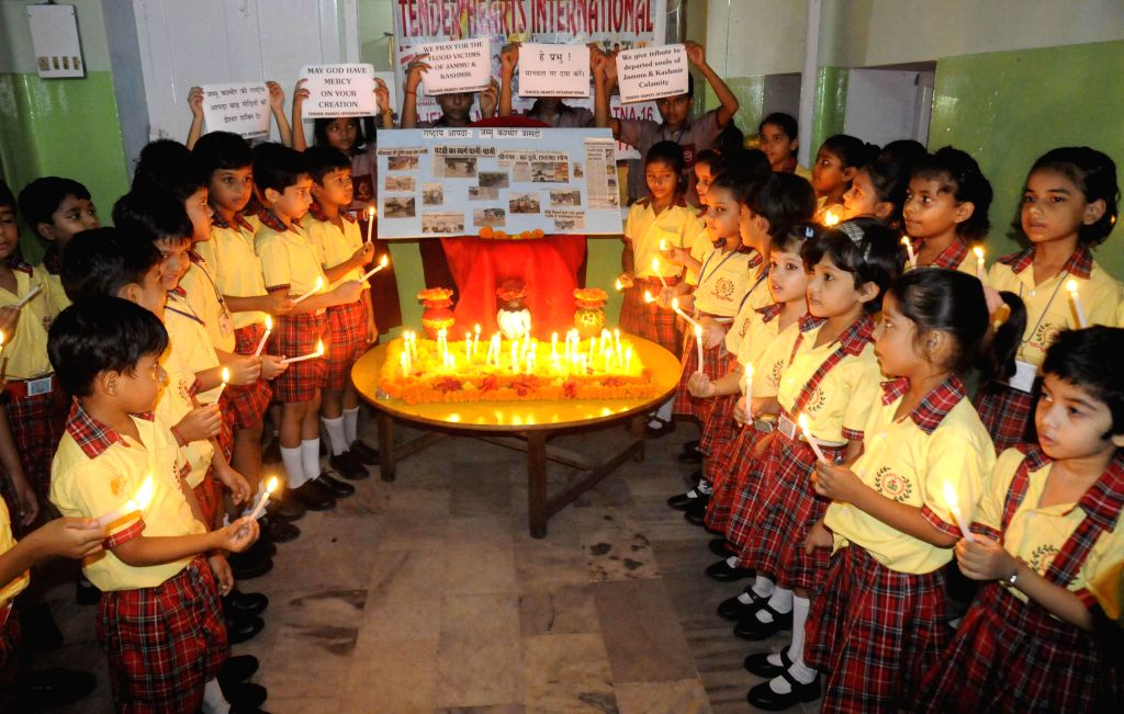School students' participate in a candlelight vigil to pray for the well-being of those marooned in Kashmir floods, in Patna on Sept 8, 2014.