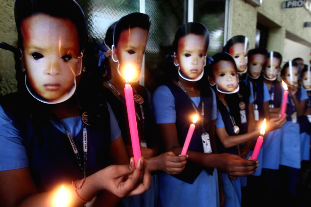 School students participate in a candlelight vigil to pay tributes to the two-year-old boy Sujith Wilson who died after falling into a borewell in Tamil Nadu's Tiruchirappalli district; at ...